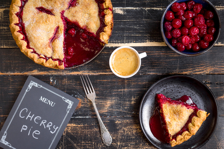 flaky: Homemade sliced cherry pie with flaky crust, cup of coffee, bowl with cherries and menu chalkboard on the black wooden table. Top view