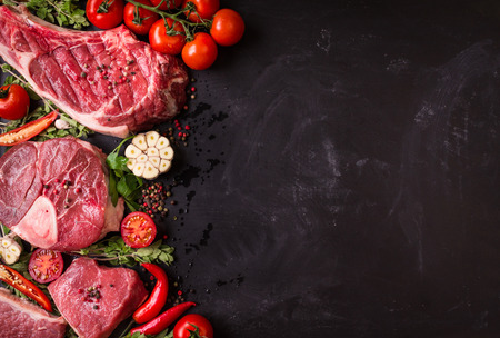 eye for an eye: Raw juicy meat steaks ready for roasting on a black chalk board background. Rib eye steak on the bone, veal shank (ossobuco), fillet with cherry tomatoes, hot pepper and herbs. Space for text