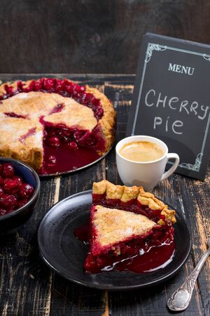 cherry pie: Slice of homemade cherry pie, cup of coffee, bowl with cherries and menu chalkboard on the black wooden table