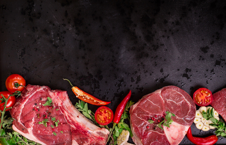 Raw juicy meat steaks ready for roasting on a black chalk board background. Rib eye steak on the bone, veal shank (ossobuco), fillet with cherry tomatoes, hot pepper and herbs. Space for text