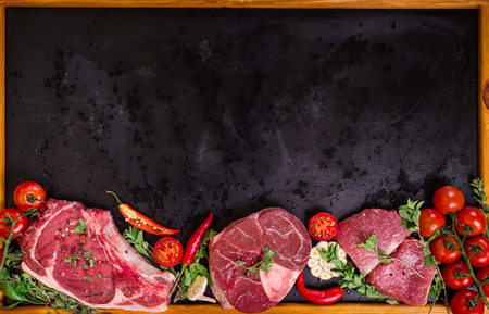 eye for an eye: Raw juicy meat steaks on a black chalk board background with wooden frame. Rib eye steak on the bone, veal shank (ossobuco), fillet with cherry tomatoes, hot pepper and herbs. Space for text