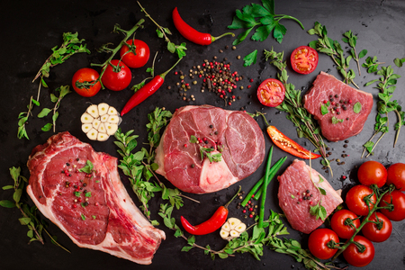 Different types of steaks set. Assorted raw meat on a black chalk board background. Rib eye steak on the bone, veal shank (ossobuco), fillet with cherry tomatoes, hot pepper and herbs.