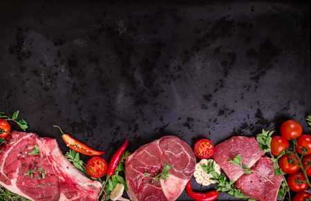 Raw juicy meat steaks ready for roasting on a black chalk board background. Rib eye steak on the bone, veal shank ossobuco, fillet with cherry tomatoes, hot pepper and herbs. Space for text