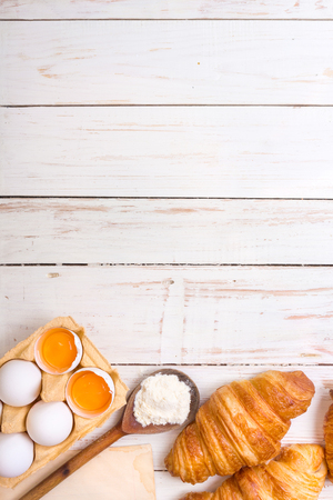 Freshly baked croissants with flour, wooden spoon, piece of paper, eggs and egg yolks in a carton tray on the white wooden table. Bakingpastry background. Free space for text