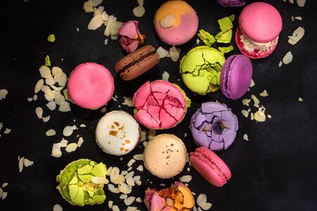 almond biscuit: Assorted colorful french macarons and almond flakes on a black background. Closeup. Top view. Concept of the baking macarons Stock Photo