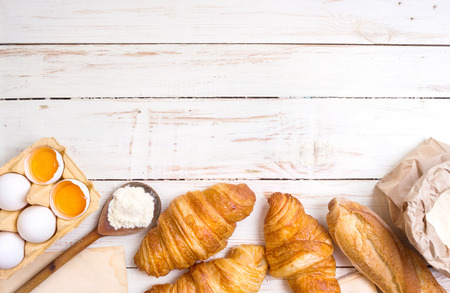Freshly baked croissants and baguette with flour, wooden spoon, piece of paper, eggs and egg yolks in a carton tray on the white wooden table. Bakingpastry background. Free space for text Archivio Fotografico