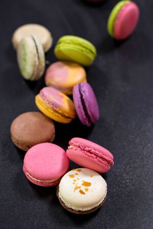 french fancy: Assorted colorful french cookies macaroons on a dark background. Closeup. Concept of the macaroons