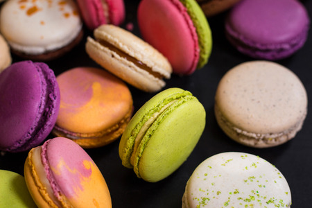 fancy sweet box: Assorted colorful french cookies macaroons on a dark background. Closeup. Concept of the macaroons