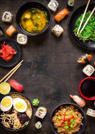 Sushi and japanese food on dark background. Sushi rolls, hiyashi wakame, miso soup, ramen, fried rice with vegetables, nigiri, salmon steak, soy sauce, ?hopsticks. AsianJapanese food frame. Overhead