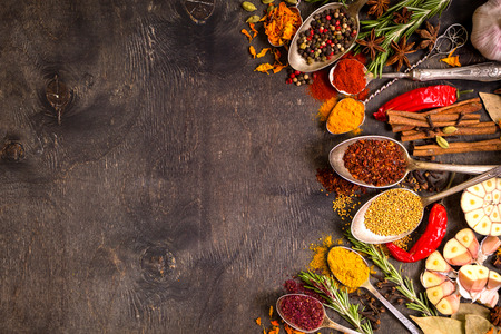 indian spice: Set of various aromatic colorful spices in old vintage spoons and herbs on a dark wooden background. Space for text. Food frame. Ingredients for cooking. Top view