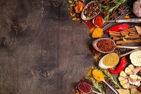 Zestaw kolorowych Vaus aromatycznych przypraw w starych zabytkowych łyżek i ziół na ciemnym tle drewniane. Przestrzeń dla tekstu. Rama Żywności. Składniki do gotowania. Widok z góry Zdjęcie Seryjne
