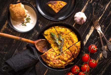 Tortilla de patatas in a pan with garlic sauce aioli and fresh tomatoes cherry. Traditional spanish dish. Omelette with eggs, potatoes and onion. Rustic black background. Top view