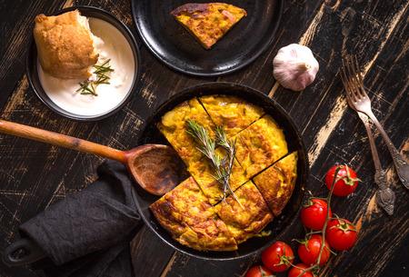 tomates: Tortilla de patatas en una sartén con la salsa alioli de ajo y tomates frescos de cereza. plato español tradicional. Tortilla con huevos, patatas y cebolla. fondo negro rústico. Vista superior Foto de archivo