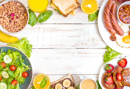 Assortment of breakfast choices. English breakfast, sausages, fried eggs, bacon, salad, granola, cheese sandwich, pancakes, chocolate cream and banana toast, coffee, fresh orange juice. Space for text 스톡 콘텐츠