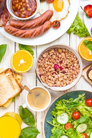 english cucumber: Brunch party. Assortment of breakfast choices. English breakfast, sausages, fried eggs, bacon, salad, granola, cheese sandwich, pancakes, chocolate cream and banana toast, coffee, fresh orange juice Stock Photo