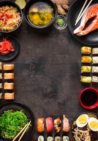 Sushi and japanese food on dark background. Sushi rolls, hiyashi wakame, miso soup, ramen, fried rice with vegetables, nigiri, salmon steak, soy sauce, ?hopsticks. Asian/Japanese food frame. Overhead
