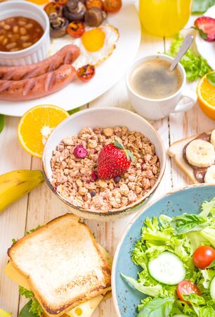 english cucumber: Assortment of breakfast choices. Granola with strawberry in a bowl and sausages, fried eggs, bacon, salad, cheese sandwich, pancakes, chocolate cream and banana toast, coffee, orange juice. Close-up Stock Photo