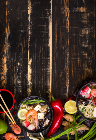 Table served with asian noodle soups in a black bowls with chopsticks, soy sauce, sliced lime, ginger on a dark textured wooden background. Space for text. Asian style dinner. Ingredients for cooking 스톡 콘텐츠