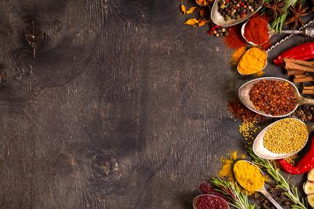 오래 된 빈티지 숟가락과 허브 어두운 나무 배경에서 다양 한 향기로운 다채로운 향신료의 집합입니다. 텍스트를위한 공간입니다. 음식 프레임. 요리