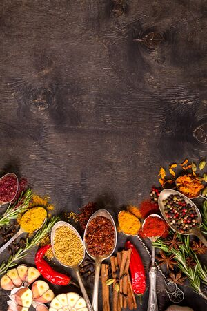 recipe background: Set of various aromatic colorful spices in old vintage spoons and herbs on a dark wooden background. Space for text. Food frame. Ingredients for cooking. Top view