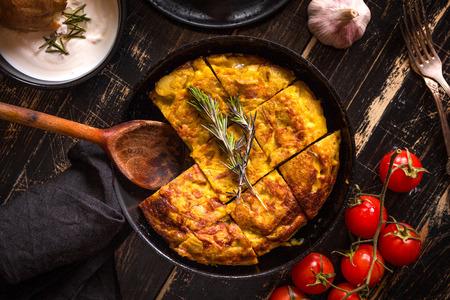토틸라 드 patatas 마늘 소스 aioli와 신선한 토마토 체리와 팬. 전통적인 스페인 요리입니다. 계란, 감자, 양파와 오믈렛입니다. 소박한 검은 배경. 평면도
