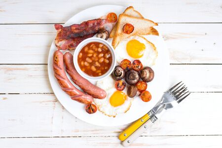 bacon baked beans: Full english breakfast with fried eggs, tomatoes, sausages, bacon, mushrooms, toasts and beans. Breakfast on a white plate with forks on the white wooden table. Top view
