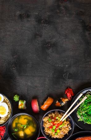 Sushi and japanese food on dark background. Sushi rolls, hiyashi wakame, miso soup, ramen, fried rice with vegetables, nigiri, salmon steak, soy sauce, Ñ?hopsticks. Asian/Japanese food frame. Overhead