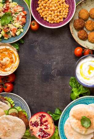 Middle eastern traditional dishes on a dark background. Doner kebap, vegetarian pita, bowl with hummus, falafel, tabbouleh bulgur salad, boiled chickpea, olive oil dip, pomegranate. Space for text