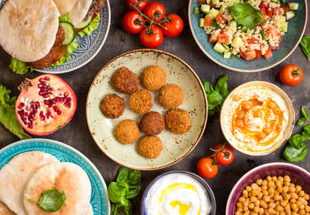 Table served with middle eastern traditional dishes. Bowl with falafel, doner kebap, vegetarian pita, hummus, tabbouleh bulgur salad, chickpea, olive oil dip, pomegranate. Top view. Dinner party Banco de Imagens - 58767718