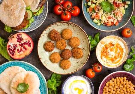 Tisch serviert mit nahöstliche traditionelle Gerichte. Schale mit Falafel, Döner, vegetarische Fladen, Hummus, Taboulé Bulgursalat, Kichererbse, Olivenöl-Dip, Granatapfel. Draufsicht. Tischgesellschaft