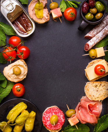 spanish tapas: Mix of different snacks and appetizers. Spanish tapas on a black stone background. Tapas bar. Space for text. Deli, sandwiches, olives, sausage, anchovies, cheese, jamon, pepper, tomatoes. Top view Stock Photo