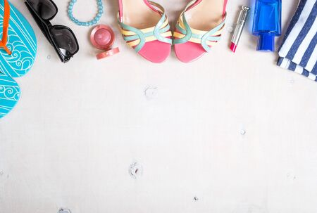 Feminine summer background. Set of summer women's accessories: sunglasses, shoes, slippers, blue striped bag, pink lipstick, blush, perfume on white wood background. Vacation/travel. Space for text