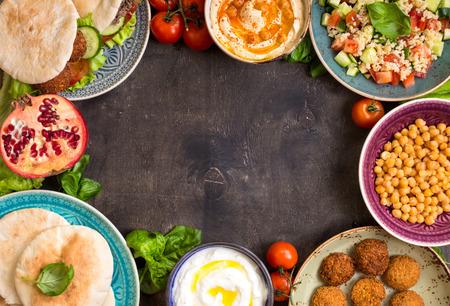 어두운 배경에 중동 전통 요리입니다. Doner kebap, falafel와 피타, hu mmus, falafel, tabbouleh bulgur 샐러드, 삶은 병아리 콩, 올리브 오일 딥, 석류와 그릇. 텍스트 스톡 콘텐츠