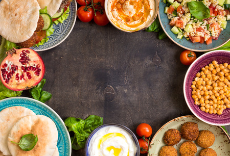 Middle eastern traditional dishes on a dark background. Doner kebap, pita with falafel, bowl with hu mmus, falafel, tabbouleh bulgur salad, boiled chickpea, olive oil dip, pomegranate. Space for text