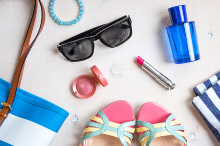 Set of summer women's accessories: sunglasses, shoes, slippers, passport, blue striped bag, pink lipstick, blush, perfume on white wood background. Feminine vacation/travel/sea objects. Top view