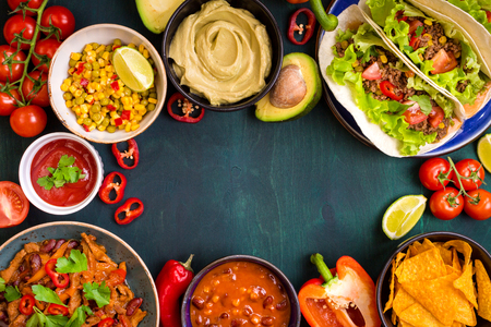 Mixed mexican food background. Party food. Guacamole, nachos, fajita, meat tacos, salsa, peppers, tomatoes on a wooden table. Space for text. Top view. Tex-mex cuisine. Assorted appetizers. Food frame