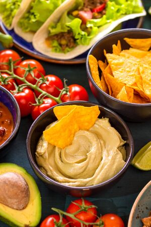 Mixed mexican food. Party food. Guacamole, nachos, fajita, meat tacos, salsa, peppers, tomatoes on a wooden table. From above. Tex-mex cuisine. Assorted appetizers. Cuisine of Mexico. Selective focus Stock Photo