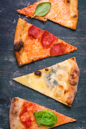 different types of cheese: Assorted pizza slices. Margherita, pepperoni, four cheese pizza. Top view. Different types of pizza on the textured old wooden table.