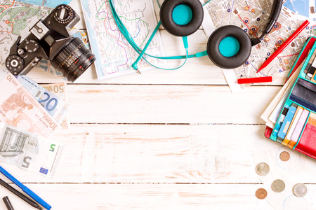 Camera, touristic maps, headphones, wallet with credit cards, phone, colorful pens, euro banknotes and coins on the white desk. Travel background. Journey planning. Tourist essentials. Space for text Stock Photo