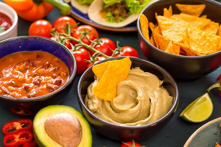Mixed mexican food. Party food. Guacamole, nachos, fajita, meat tacos, salsa, peppers, tomatoes on a wooden table. From above. Tex-mex cuisine. Assorted appetizers. Cuisine of Mexico. Selective focus Foto de archivo
