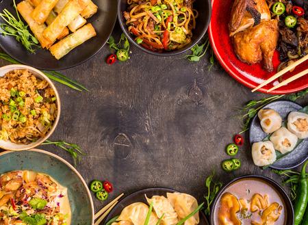 中華料理暗い背景。ラーメン、チャーハン、餃子、北京ダック、飲茶、春巻き。有名な中国料理を設定します。テキストのためのスペース。平面図