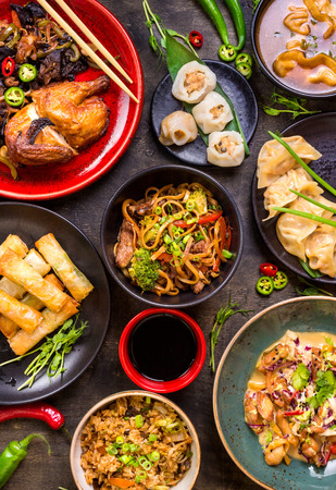 Assorted Chinese food set. Chinese noodles, fried rice, dumplings, peking duck, dim sum, spring rolls. Famous Chinese cuisine dishes on table. Top view. Chinese restaurant concept. Asian style banquet