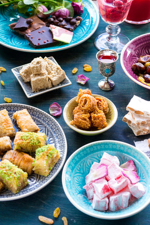 sherbet: Set of assorted traditional eastern desserts. Different Arabian sweets on wooden table. Baklava, halva, rahat lokum, sherbet, nuts, pistachios, dates, raisins, kadayif in a colorful plates. From above Stock Photo