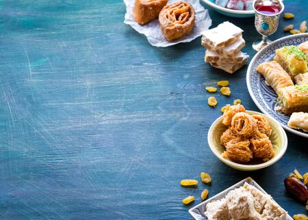 Background witn assorted traditional eastern desserts. Different Arabian sweets on wooden table. Baklava, halva, rahat lokum, sherbet, nuts, dates, raisins, kadayif in colourful plates. Space for text