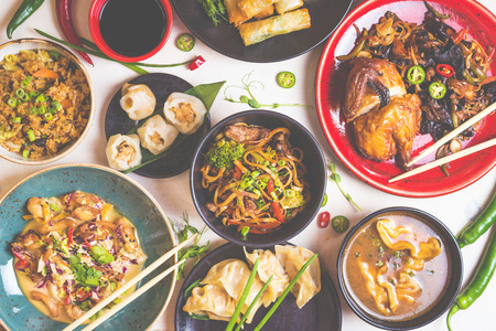Assorted Chinese food set. Chinese noodles, fried rice, dumplings, peking duck, dim sum, spring rolls. Famous Chinese cuisine dishes on white table. Top view. Chinese restaurant concept. Toned image Stock Photo