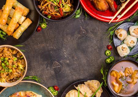 Chinesisches Essen dunklen Hintergrund. Chinesische Nudeln, Reis, Knödel, Peking-Ente, Dim Sum, Frühlingsrollen. Berühmte chinesische Küche Gerichte gesetzt. Platz für Text. Draufsicht. Chinese Restaurant-Konzept