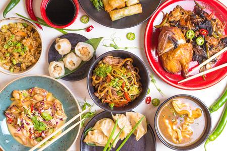 모듬 중국 음식 세트입니다. 중국 국수, 볶음밥, 만두, 북경 오리, 딤섬, 춘권. 흰색 테이블에 유명한 중국 요리 요리. 평면도. 중국 식당 개념. 아시아