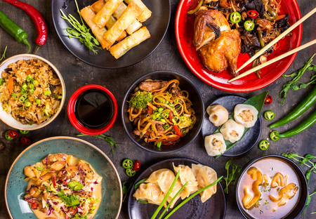 Assorted Chinese food set. Chinese noodles, fried rice, dumplings, peking duck, dim sum, spring rolls. Famous Chinese cuisine dishes on table. Top view. Chinese restaurant concept. Asian style banquet Zdjęcie Seryjne - 62444805