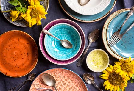 빈티지 여러 가지 빛깔 된 빈 접시와 해바라기와 어두운 회색 린 넨 식탁보에 그릇. 골동품 숟가락과 포크. 테이블 세팅. 초라한 세련된  복고풍 스타