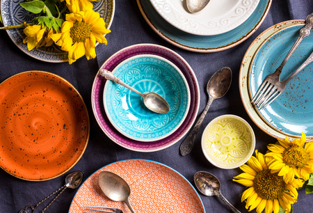 Vintage multicolored empty plates and bowls on a dark gray linen tablecloth with sunflower. With antique spoons and forks. Table setting. Shabby chic/retro style. Top view. Rustic kitchen